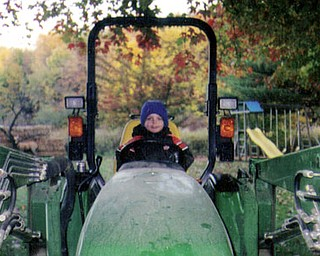 Dylan George, son of Angela and Erik George and grandson of Cheri and Stan Saveet of New Midletown, gets a ride on grandpa's tractor.