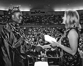 Dwaine Thomas accepts his diploma from board of education member Lauri Kuszmaul.