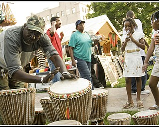 Touba Ndiaye draws a crowd playing the West African Gumbe drums he brought to sell.