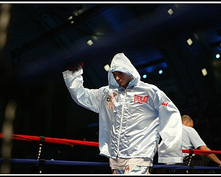 Hooded, Kelly Pavlik enters the ring.