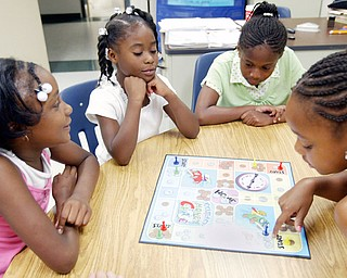Youngstown Community School students left-to-right Jalaya Kitchen, 7, Johnae Coleman, 7, Nyla Bass, 8, and Jay'Lynne Armour. 8. play a board game during a student at Youngstown Community School,  during a 4 week summer intervention program at the school Wed 7-9-08. The program which ends Friday 7-11 stresses math and reading skills  to improve test scores and foster a love of learning. About 45 students participated in the program.