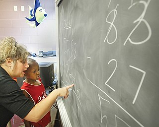 Cheriese Farkas, a teacher at Youngstown Community School works with Markies Hopkins, 7, a student at the school, on a math problem during a 4 week summer intervention program at the school Wed 7-9-08. The program stresses math and reading skills to improve test scores and foster a love of learning. About 45 students participated in the program.