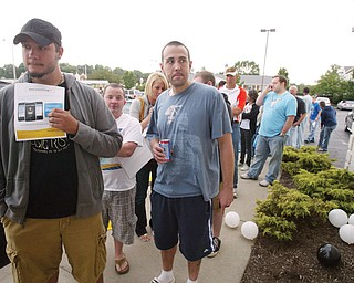 Tim Lockso, left, of Hubbard and Doug McClintock of Boardman were among a group of people lined up outside the AT&T store in Boardman Friday to purchase iPhones. Some waited overnight in parking lot.