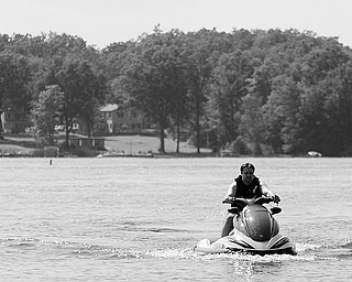 "[7.5.2008] Eric Houck, of Boardman, rides a jetski July 5, 2008 at Lake Milton where his in-laws have a place on the lake. Houck hasn't noticed a decline in jet ski usage on the lake, but has noticed ""quite a few less boats."""