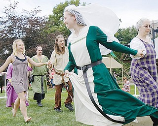 [7.12.2008] Laura Huffman, of Wadsworth, and Jenny Blazek, of Farmington, dance the Trenchmore beside a tent belonging to the Society for Creative Anachronism at the YSU Summer Festival of the Arts along Wick Ave. Saturday afternoon. The group of medieval enthusiasts recreate the tournament style fighting, craft making, drama, music, camping, and cooking of the era citing the importance of learning history beyond simply reading about it and by experiencing it as well. More information can be found at the local chapter's website www.rivenvale.org/ or the national website www.sca.org.