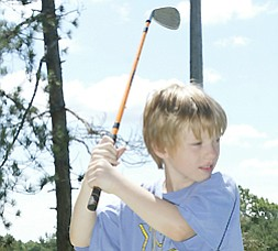 Andy Garr, 8, of Canfield tees off at Mill Creek Par 3 during Golf Camp.