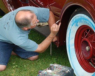 "Guy Shively, of Austintown, pinstripes a 1933 Packard at The 19th Annual National Packard Museum Car Show, ""Boss of the Road, Beauty of the Boulevard."" Pinstriping, traditionally, is done freehand, as Shively is doing here."