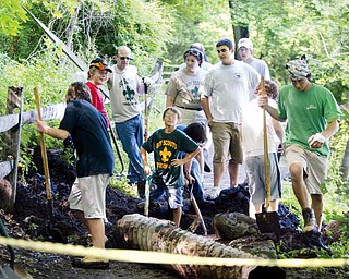 LOTS OF HELP: Members of Scout Troop 40 of Girard, including Jordan Vigorito, third from right, woork on Vigorito's Eagle Scout project at the Lily Pond in Mill Creek Park. They are fixing exposed drainage pipes on the trail surface.