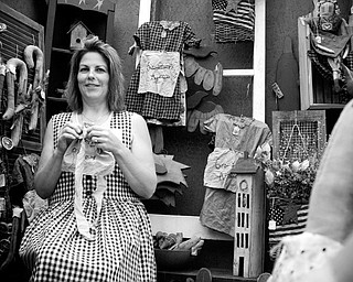 A STITCH IN TIME: Debbie Forgac of North Lima stitches an apron while dressed in traditional Shaker apparel. She took part in the Shaker Woods Festival in Columbiana on Sunday.