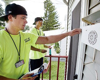 DOOR TO DOOR: Girard meter readers Ben Belcik, left, and Brien Golden try to reach the occupant of this Ohio Avenue home. Like with most attempts by readers in the city, it was unsuccessful Monday. No one was home.