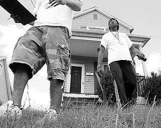 ANOTHER ATTEMPT:  Girard meter readers Ben Belcik, left, and Brien Golden leave an Ohio Avenue house after unsuccessfully attempting to gain access to the water meter inside the home. The notification of their attempt hands from the mailbox in the background.