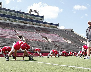 STAMBAUGH STRETCHING: Youngstown State University football head coach JOn Heacock patrols as his players prepare for Monday's practice.