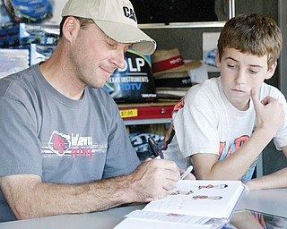 Dave Blaney signs an autograph as his son Ryan, 14, looks on at Sharon Speedway