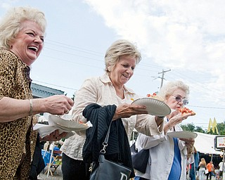 DELICIOUS: Friends Gloria Conman of Austintown, left, Jan Maglaughlin of Boardman and Lucille Brown of Youngstown enjoy a laugh and a slice of pizza during the Brier Hill Italian Festival in Youngstown on Thursday. The festival continues today through Sunday on Calvin and Victoria Streets.