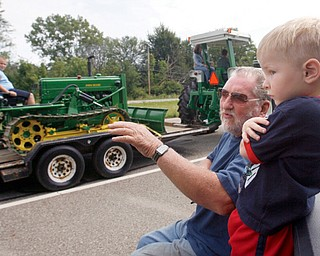BIG WHEEL: Jim Wright and great-grandson Adrian Wilkes, 3, both of Braceville, watched an antique tractor parade Thursday afternoon along U.S. Route 422. The parade kicked off the annual show of the Antique Tractor Club of Trumbull County.