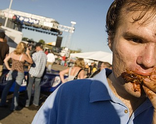 Sean Boughner, 22, of Boardman enjoying a rack of ribs at the Miller Lite National Rib Cook-Off Saturday, August 16, 2008 outside the Chevy Centre. Daniel C. Britt.