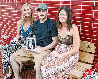 FAMILY AFFAIR: From left, Siblings megan Lewis, 27; Brian Charles, 23; and Molly Charles, 26, site outside the Girard Fire Department where their Father, John Charles, wass a firefighter for more than 20 years. He died from lung cancer last year. The memorial bench has his name engraved on it.