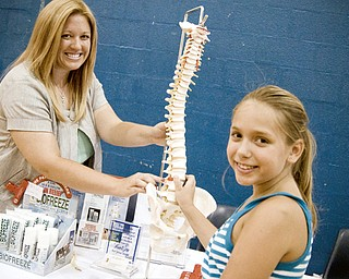 EXPERTISE: Chiropractor Dr. Amy Dahl of Austintown gives Rachael Whitney, 10, of Girard, a lesson on the human spine during the Family Fit Fair at Austintown Fitch High School