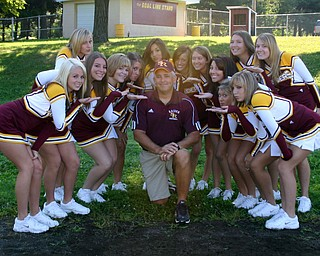 """""""South Range Coach Dan Yeagley takes time to pose with the Varsity cheerleaders at a recent team photo day."""""""
