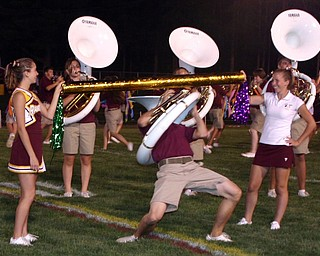 """""""Senior Jake Fry successfully limbos WITH A TUBA during the South Range Raider Band show at halftime Friday evening.  Senior flagline members Whitney Gould and Lyndsey Cramer hold the limbo pole."""""""