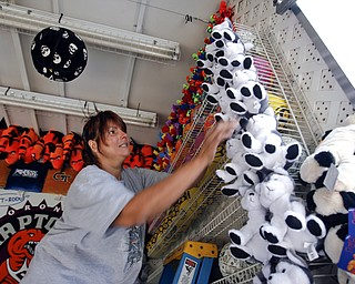 Alice Durst of Akron arranges stuffed animals at the basketball hoop game.