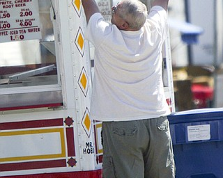 HANGIN in THERE - Bob Taylor of Cortland hangs his signs on his booth at the Canfield Fair - the Fair opens tomorrow - robertkyosay