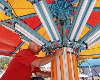 Bob Thompson of Wintersville and an electrician for Bates Bros. Amusement checks a balast on a ride in Kiddie Land