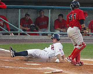 SCRAPPERS - (10) Tim Fedroff slides in to home as (56) Christian Rosa looks on during their game Tuesday night.
