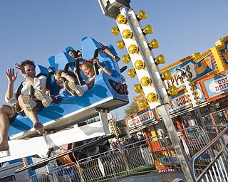Zach May, 29, of Salem, left, bounces barefoot at the Canfield Fair with neice Mackenzie May, 6, of Salem and Katie Bowmen, 6, of Canfield. They were on a Mega Bounce ride. Daniel C. Britt.