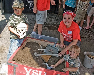 Edwina Baier, a senior Youngstown State University anthropology major, helps Joe Winters, 4, and Jack Winters, 2, both of Knox, Pa., dig for artifacts and one real skull hidden in the box until unearthed by brooms and trowels.