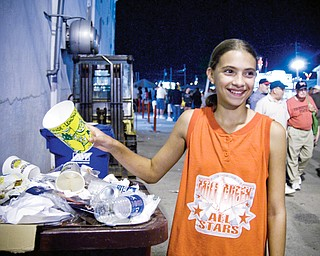 HEAPING: Megan Sefehik, 12, of Austintown, drops off garbage into one of the many receptacles around the Canfield Fair.