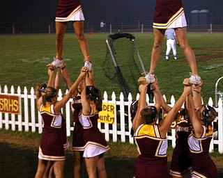 """""""Varsity Cheerleaders, Danielle Pendice and Whitney Gould, stand high to cheer on the South Range Raiders."""""""