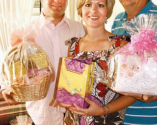 GENEROSITY: Scott Weimer, with his sister, Holly Watts, and their father, Richard Weimer, show off the donated gift baskets that will be raffled off on a bus tour that Watts is organizing to New York City. The Proceeds from the raffle and bus tour will benefit the Nancy L. Weimer Scholarship Fund named for the Weimer family matriarch who passed away from a brain tumor in December.
