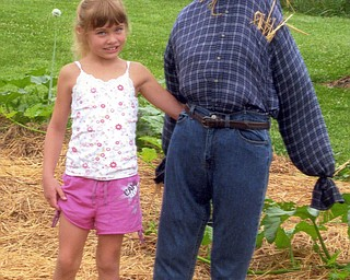 Natashia Salmen, 7, of Leetonia is rightfully proud of her scarecrow and her vegetables, which she enters in the Canfield Fair. Her grandmother, Nora Salmen of Columbiana, points out that these veggies are all Natashia's because she planted, tended and harvested everything.