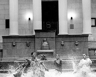WATER FUN: From left, Juan Rivera, Emanuel Morales, Steven Rivera, Ramon Soldana and Reynaldo Morales, race in the flooded water fountain of the Rutgers University Art Center in Camden, N.J. A flood watch was in effect until this morning because of Tropical Storm Hanna.