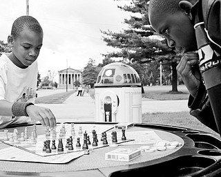 A MEETING OF THE MINDS: Ce'Andre Backus, 10, of Youngstown, left, plays chess with Kyron Lee, 12, of Youngstown as Star Wars' R2D2 tech-celebrity observes at the Stop The Violence block party in Youngstown's Wick Park.