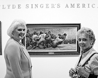A HIT: Jaque Brauninger, left, of Hubbard and Dixie Booth of LIberty examine Clyde Singer's football painting at the Butler Institute of American Art in Youngstown.