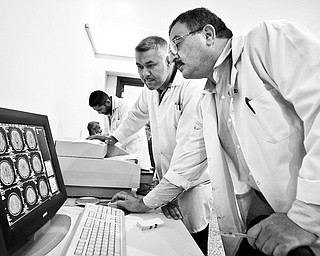 BACK TO WORK: An Iraqi doctor who returned from exile in Jordan in July, right, examines MRI scans with a colleague at a hospital in the Tunis area of northern Baghdad, Iraq. They asked that their names not be published due to security concerns.