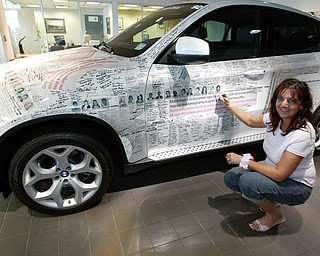 CRUISING: Teresa Kirkland signs the signature vehicle as this year's honoree before taking a BMW Series 6 convertible for a spin.