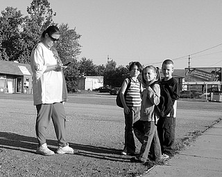 WATCHING AND WAITING: Penny Rogers supervises as, from left, Arrianna Buell, 7, Rose Buell, 5, and Dustin Rogers, 5, wait for their bus near Freddie's Diner in Warren where a fatal shooting occurred last month. Residents near the diner say the neighborhood is full of violence and prostitution, but economics make it hard to move elsewhere.