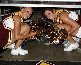 """""""Jordan Stear and Christina Oddo, South Range cheerleaders, try to stay dry at halftime of the South Range/Marlington game."""""""