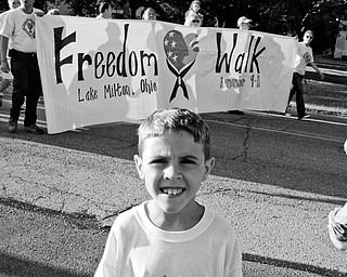 COMMUNITY ORGANIZER: Colton Lockner, 11, of Lake Milton, leads a crowd down the home stretch of the Freedom Walk. Colton organized the walk, which finished at the Lake Milton VFW hall.