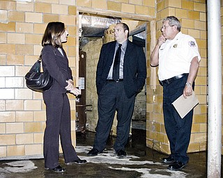 FIREHOUSE OPTIONS: Boardman township trustees Robyn Gallitto, left, and Larry Moliterno, discuss options for repairing the leaky basement of the main fire station on U.S. Route 224 with Fire Chief James Dorman, right.
