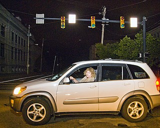 CAREFUL TRAVELER: Beth Farrell, visiting from Fairfax, Va., looks both ways at Wick and Raven avenues in Youngstown as Sunday night's winds began to abate. Power outages knocked out traffic signals all over the region, making driving difficult, especially for out-of-towners.