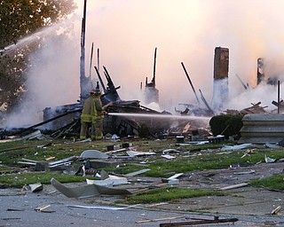 A neighboring residence caught fire after a house on the corner of Townsend and Washington Streets in Girard exploded Thursday, July 18, 2008. Photo by Steve Meyers.