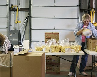 L-R Beverly Genova of Youngstown and Second Harvest Food Bank's Operations Manager Linda Martin of Austintown, pack bags full of food for families in need on Saturday at the Salt Springs Road location.