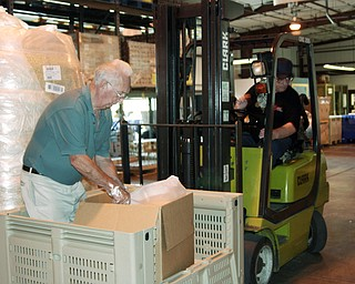 L-R Felix Lazazzera  and Bill Lusk (both of Austintown) are moving boxes of cereal to the next step where volunteers and workers will fill smaller one pound bags.