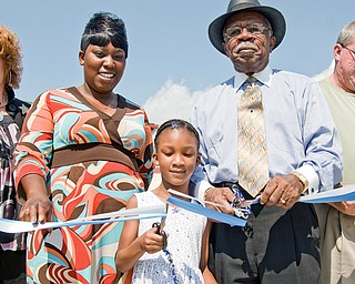 Cutting the ribbon on MLK elementary are, L-R, Cathy Dorbish, Taazmayis Briggs and her daughter Paris Marks, 6, both of Youngstown, Loch Beachum and Youngstown BOE member Mike Murphy.