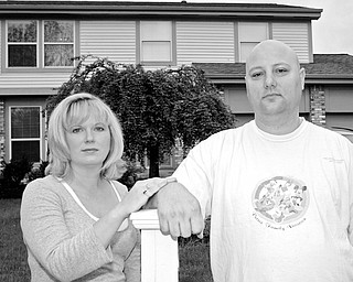 MOVING OUT: Jamie and John Petree stand in front of their home in Gahanna, Ohio, as they move out. The Petrees say that previous owner Andrew Zukowski, who had lost the house in a bank foreclosure, has tried to scare them away for eight years.