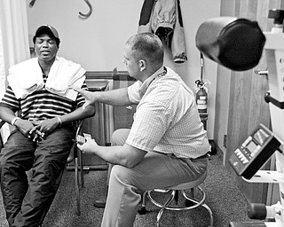 THERAPEUTIC: Youngstown veteran Robino D. Lawrence, left, works with Matt Creed in the physical therapy department of the Veterans Affairs clinic in Youngstown.